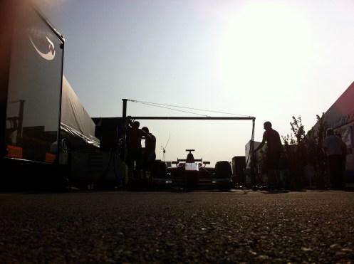 Mechanics stand over Mitch Evans' Arden car, practicing stops. © Leigh O'Gorman
