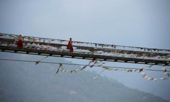 A monk on his way across the Punakha Suspension bridge. Photo: Kaushik Naik