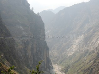 Dusty hazy view of the Old Hindustan Tibet Road cut across the face of mountain with the sheer drop down into the Sutlej river; Photo: Ameen Shaikh