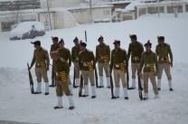 Policemen preparing for the flag hoisting ceremony in the snowfall.