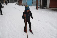 A kid skiing on a slope as the snow continues to fall.