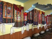 Thangkas hung on the room's wall depicting various Buddhist deities.
