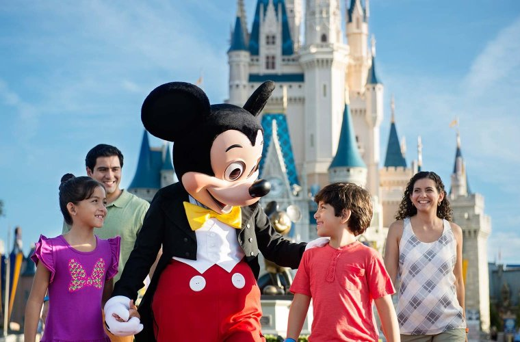 Mickey walking at Magic Kingdom with three kids. Cinderella Castle is in the background.