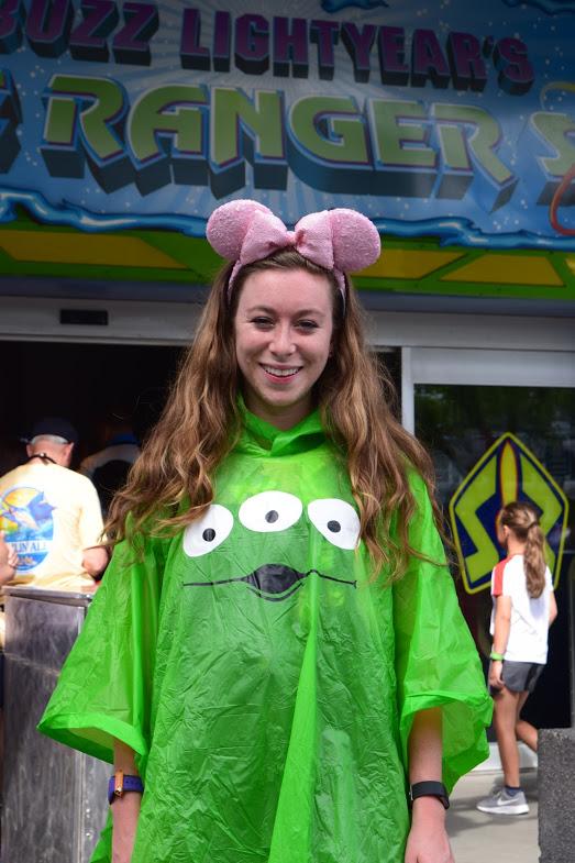 Girl wearing a green alien poncho at Magic Kingdom.