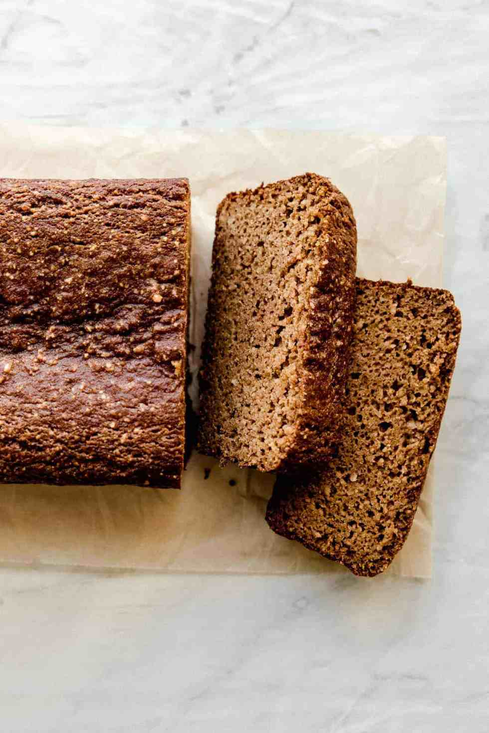 two slices of paleo pumpkin bread on brown parchment paper