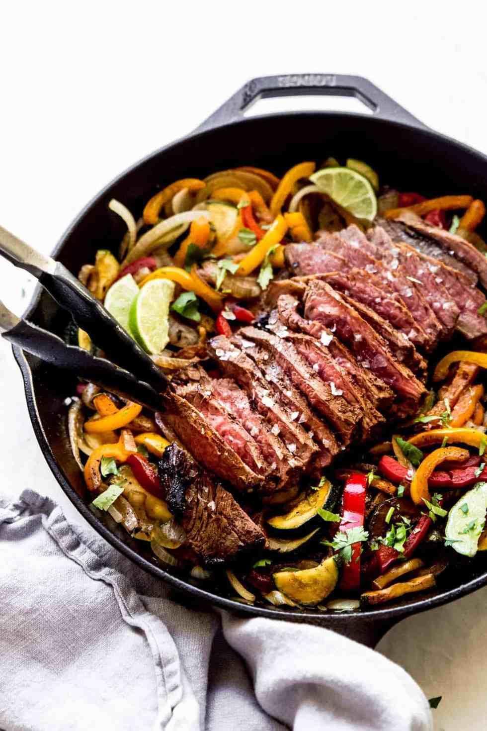 tongs picking up steak fajitas out of a cast iron pan