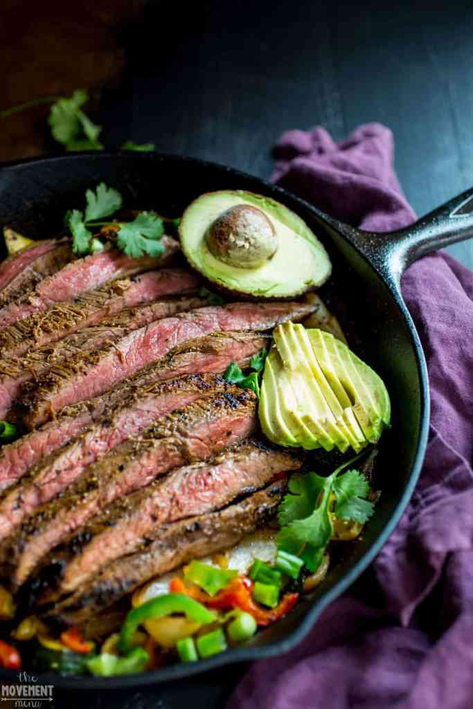 close of Whole30 steak fajitas in a cast iron pan with avocado