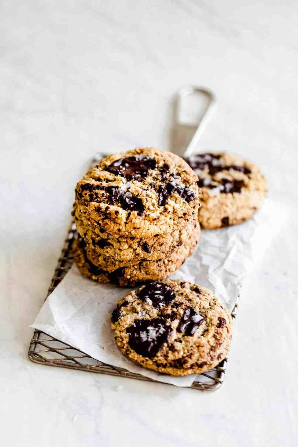 paleo chocolate chip cookies on parchment paper on a small wire rack