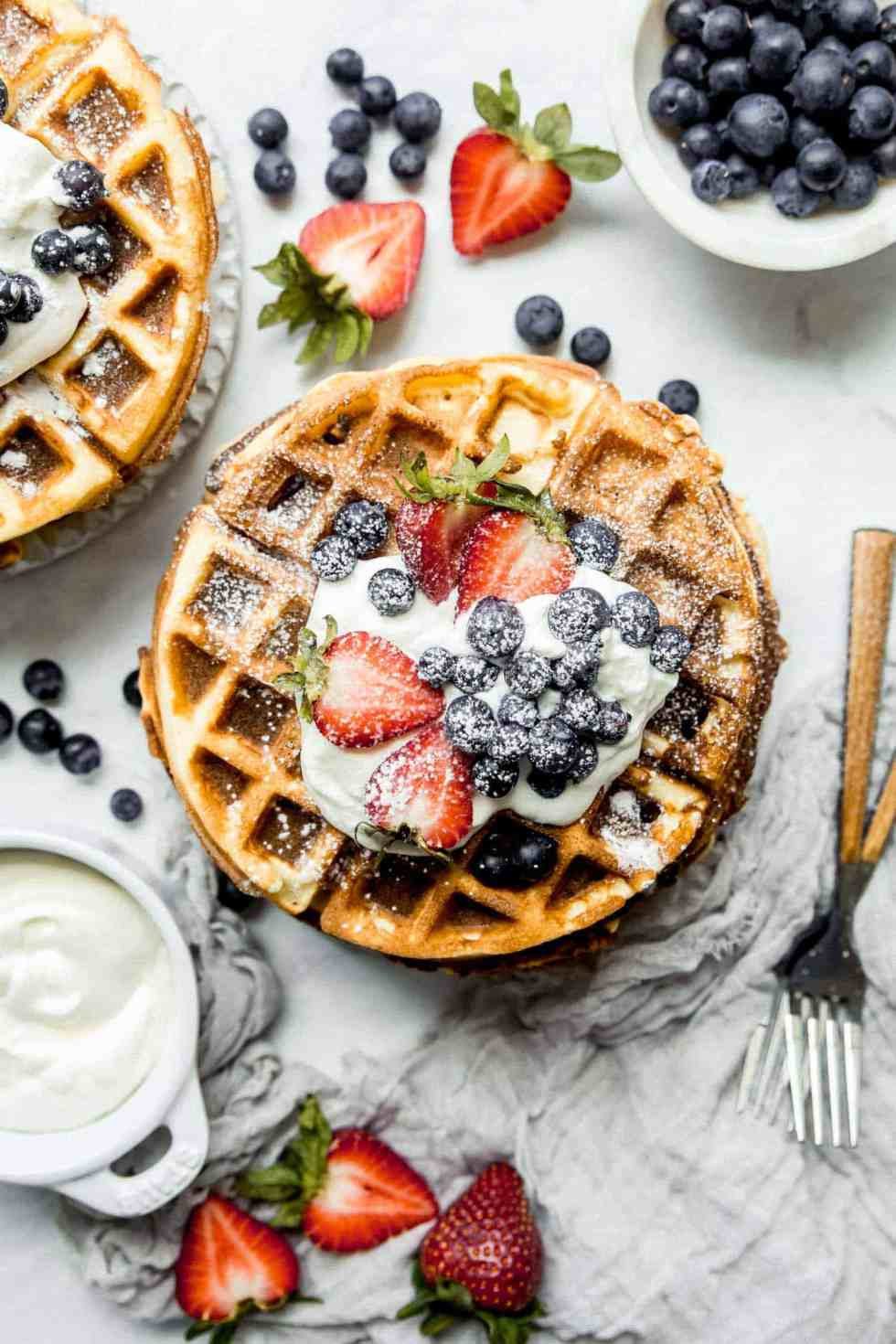 overhead shot of paleo waffles with berries and powdered sugar