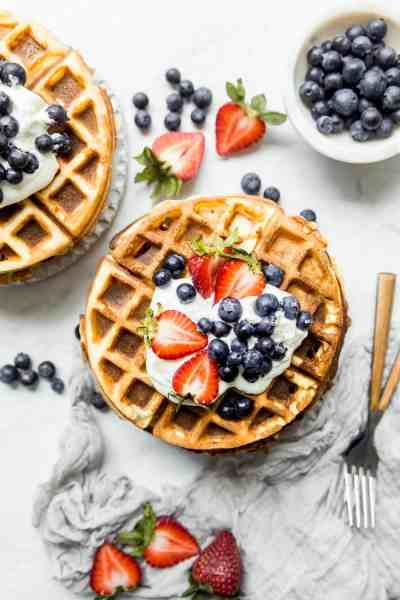 stack of waffles on a plate with berries and forks on the side