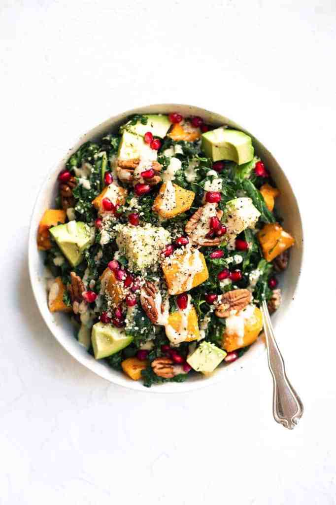 Roasted Butternut Salad with kale, avocado, pecans & pomegranate. A healthy, gluten free recipe filled with fall flavors. Easy, filling and perfect for make ahead lunches and dinners! Recipe at themovementmenu.com I healthy salads I kale salad I gluten-free salads I butternut squash salad I easy dinner salad I The Movement Menu II #dinnerrecipes #deliciousfood #healthyfood