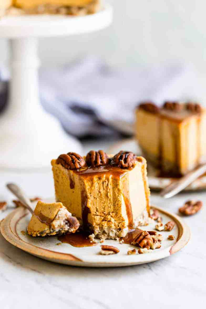 pumpkin cheesecake topped off with caramel on a plate with a fork