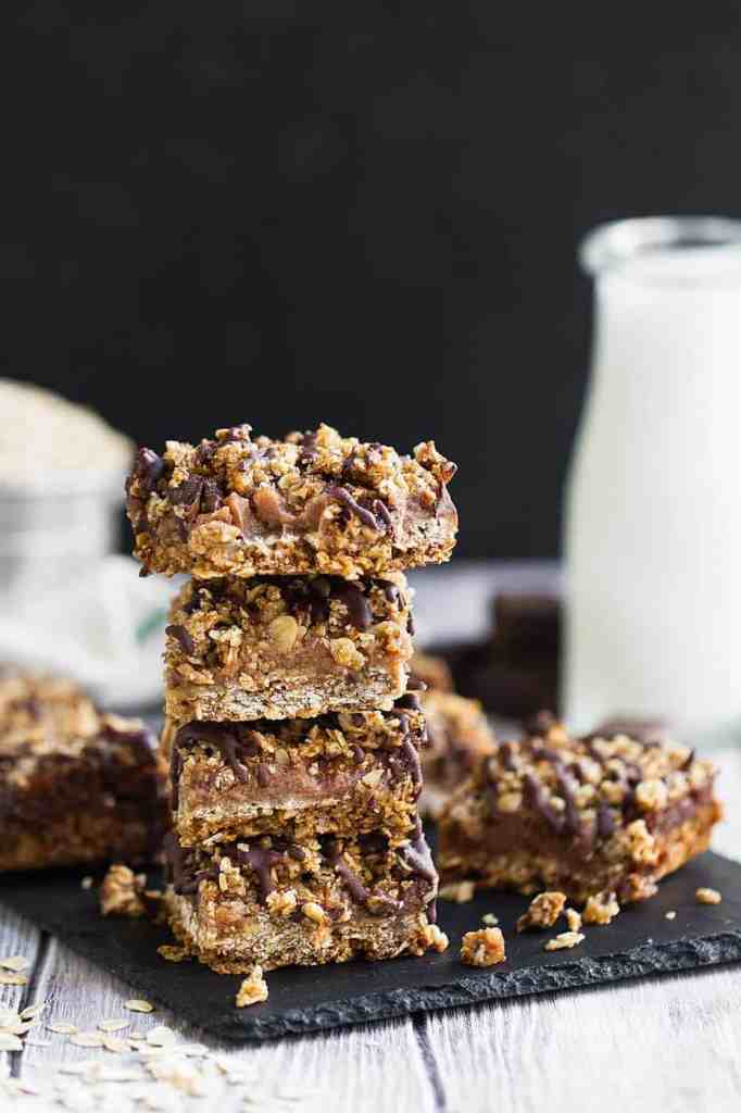 Vegan double chocolate oat bars that are sweetened with dates and topped off with a dark chocolate drizzle. Chocolate oat bars. Healthy gluten free oat bars. Gluten free desserts recipes. Gluten free oat bars.