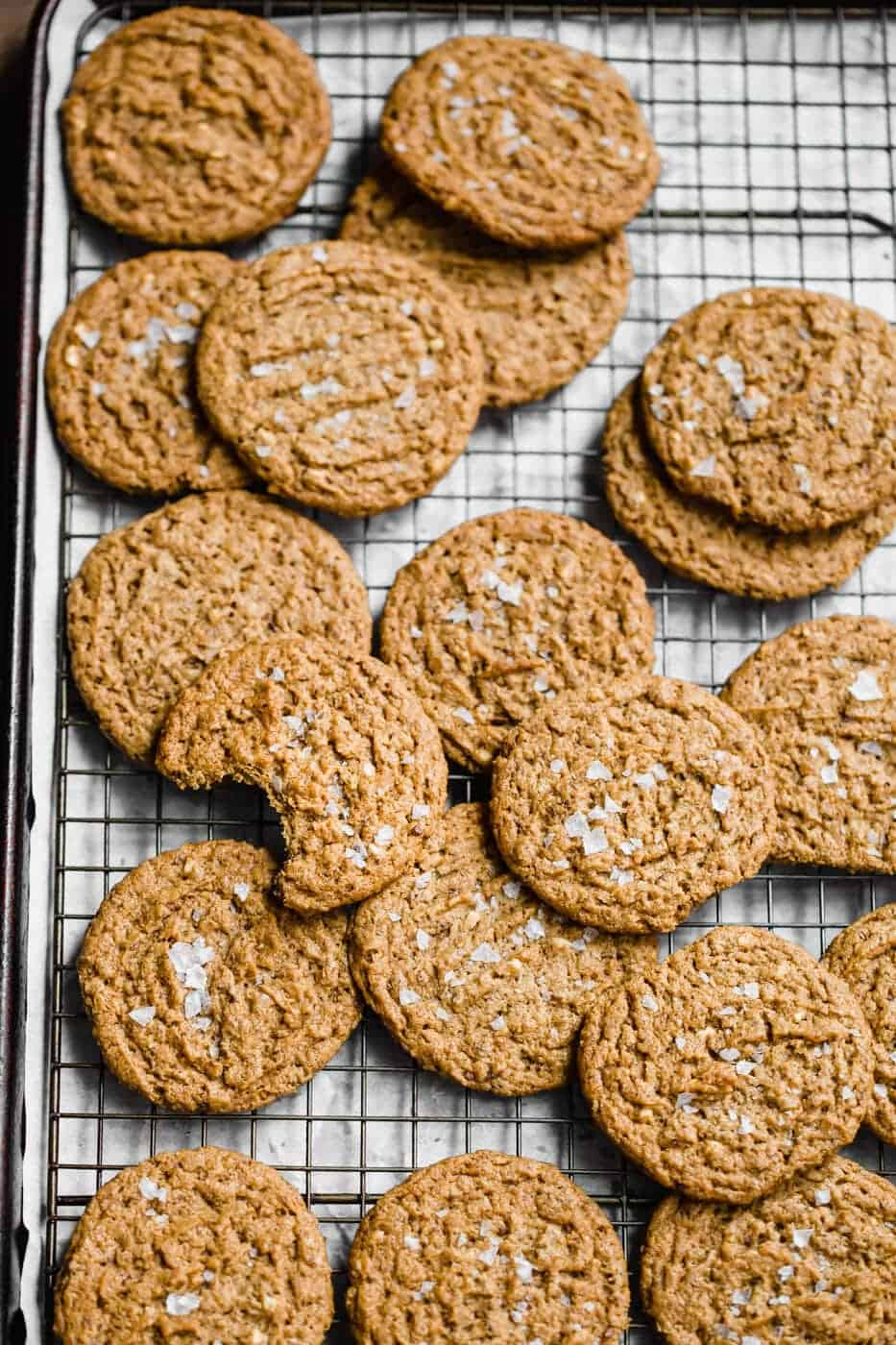 a lot of almond butter cookies on a wire rack with salt on top