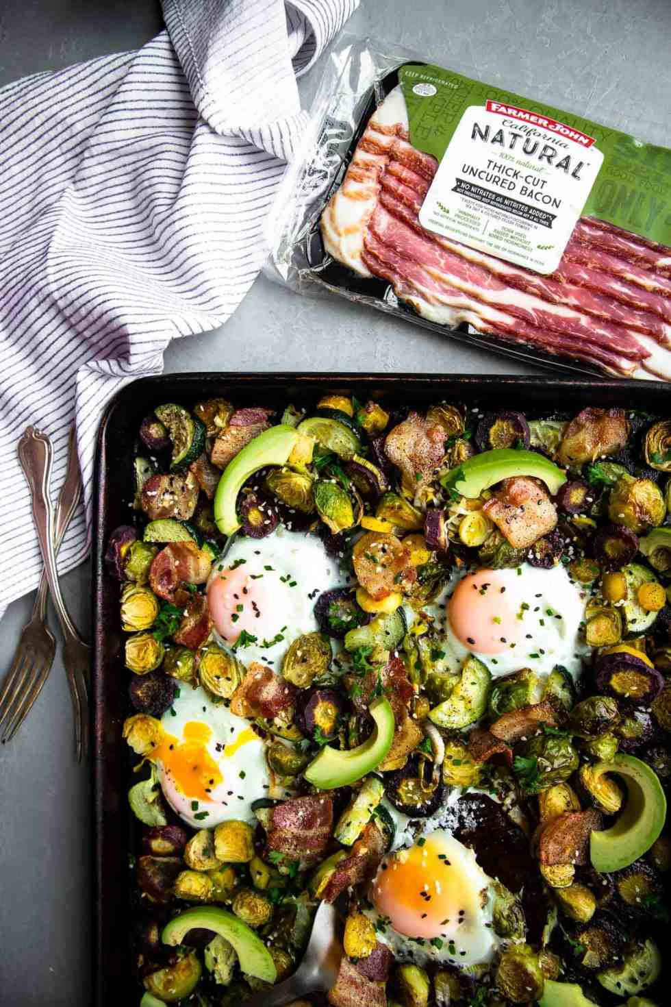 a paleo one pan breakfast on a sheet pan with eggs, bacon, avocado and vegetables
