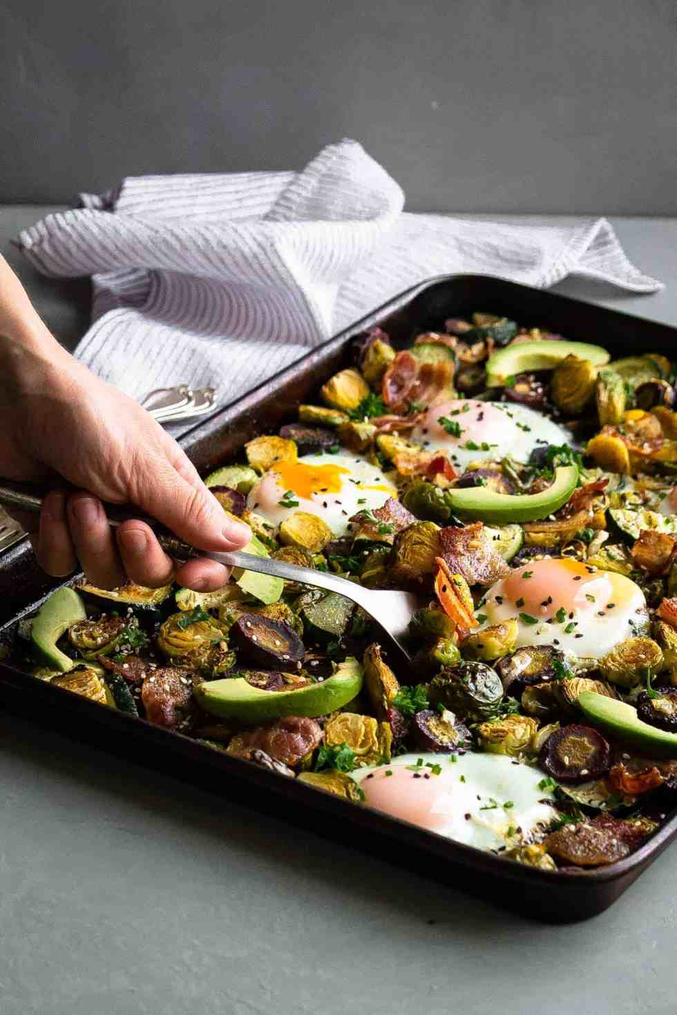 a paleo one pan breakfast on a sheet pan with eggs, avocado and vegetables scooping out