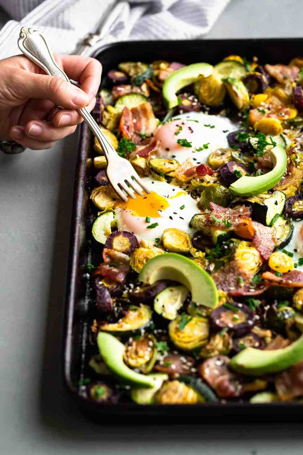 a paleo one pan breakfast on a sheet pan with eggs, avocado and vegetables and a fork digging in