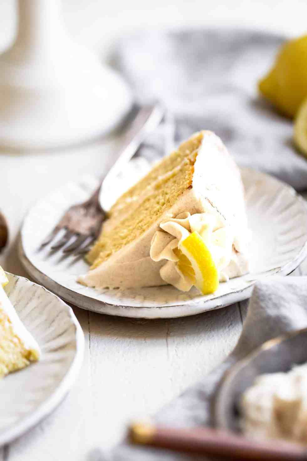 sugar free lemon cake with vanilla buttercream on a plate with a fork