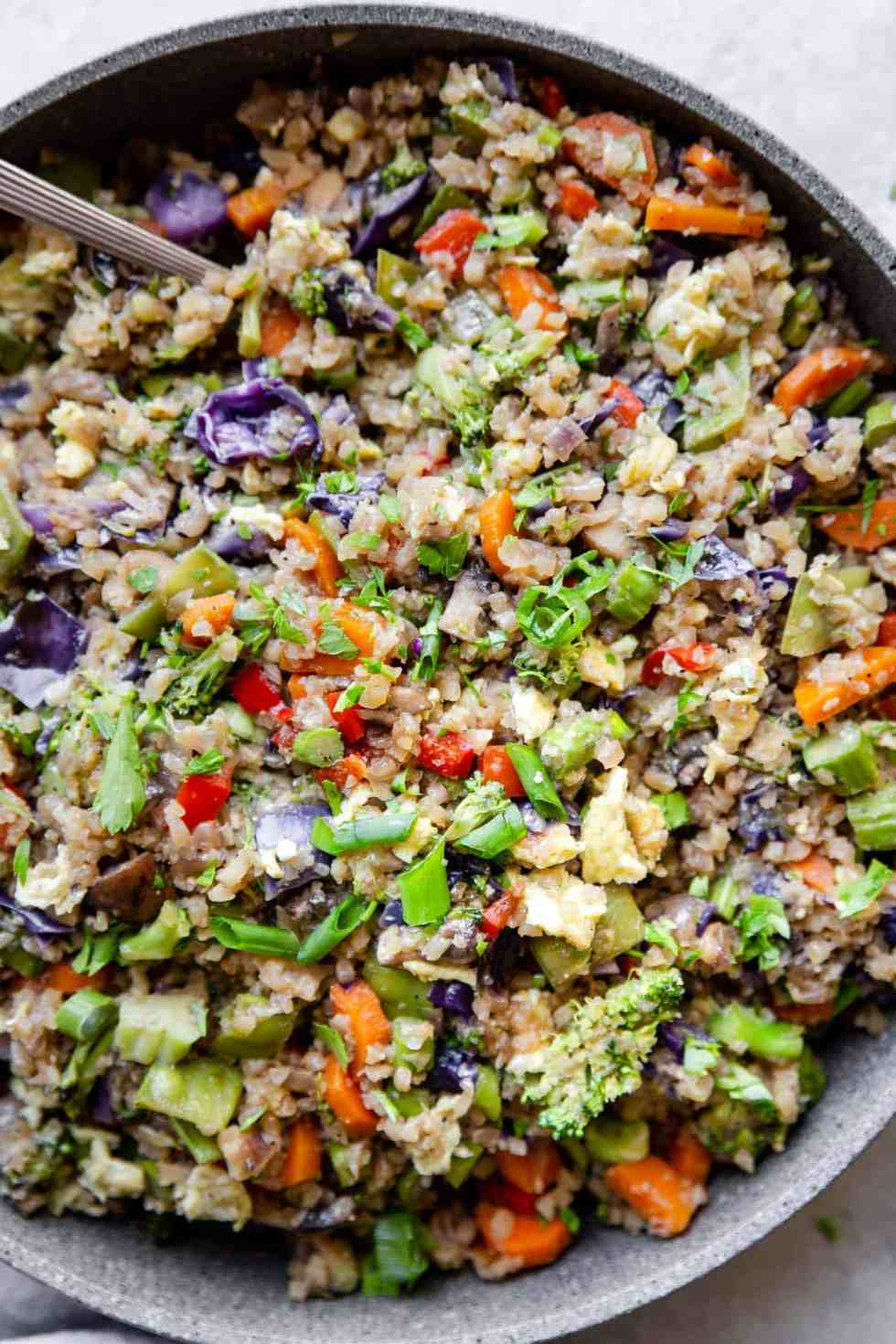 overhead shot of cauliflower fried rice in a big pan with a spoon inside