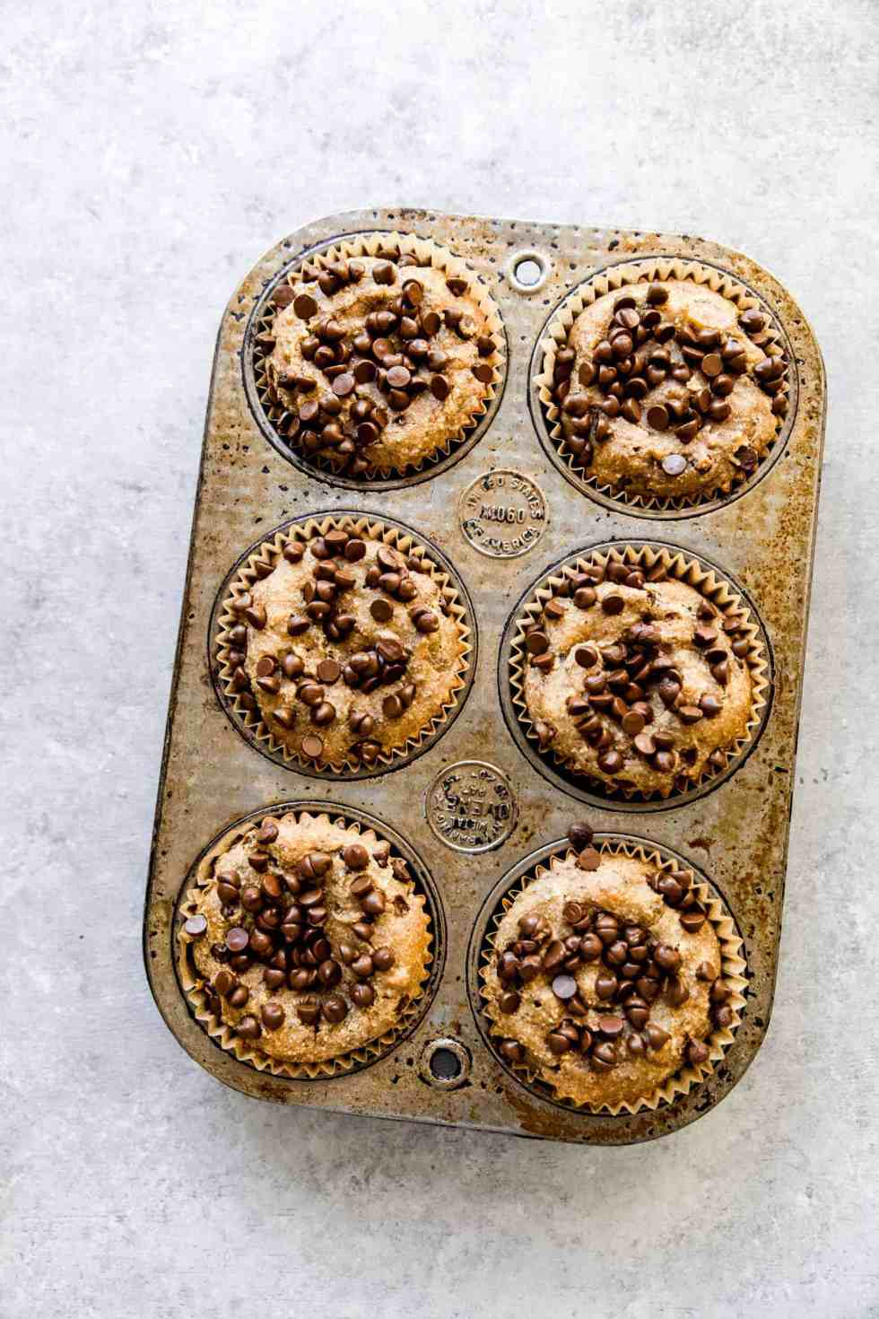 6 banana muffins with chocolate chips on top in a muffin tin