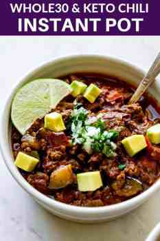 big bowl of chili with a lime on top and diced avocado