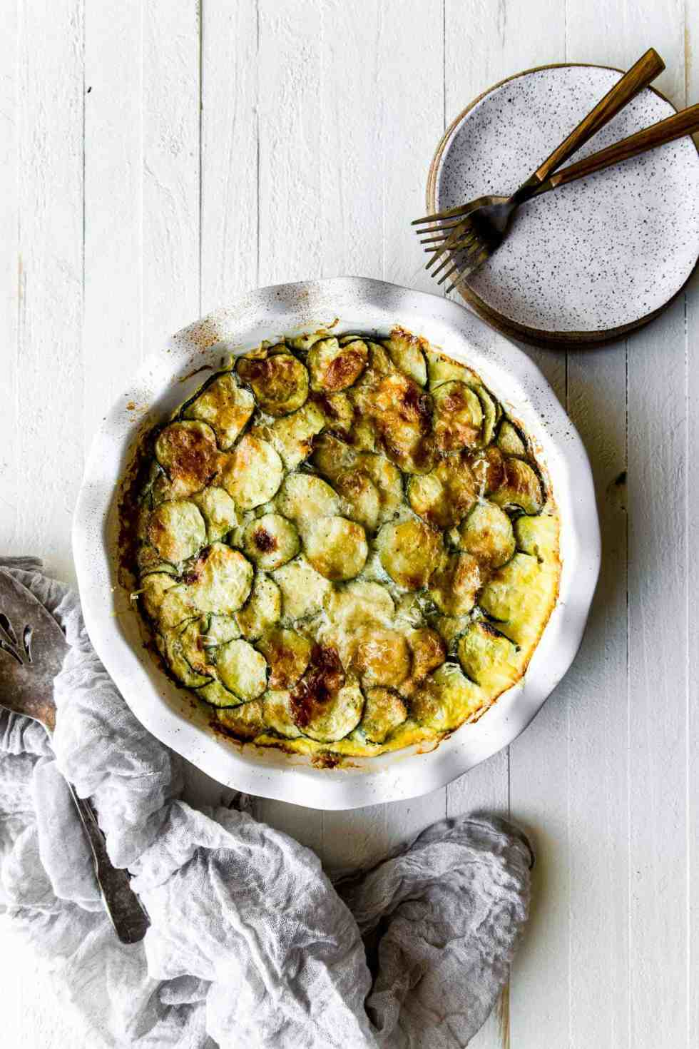 zucchini casserole in a white pan with a napkin and plates on the side