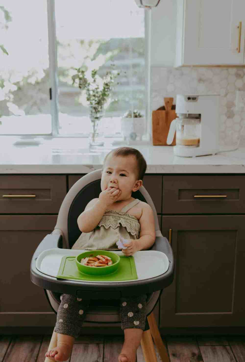 baby eating food in a white and gray high chair in the kitchen