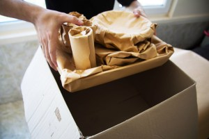 Wrapped items being placed in a cardboard box