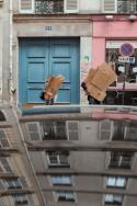 Two people holding cardboard boxes in the street