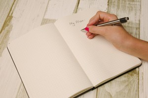 A person writing a plan in a notebook before moving on short notice