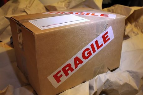 A cardboard boxc with the sticker saying fragile on it.