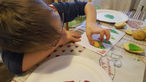 Dipping the potato into the paint and then onto the card.