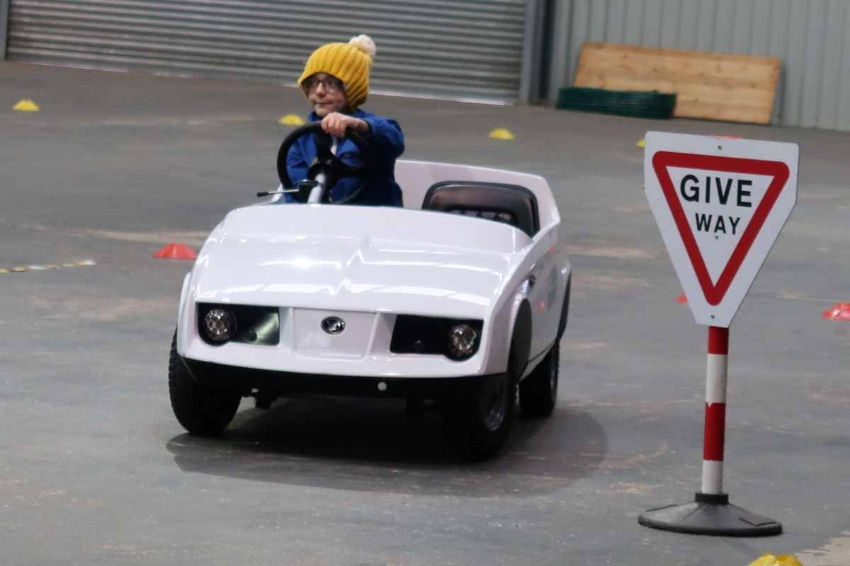 Older boy child driving in a white firefly car. Which is a purpose built car to teach them how to drive.