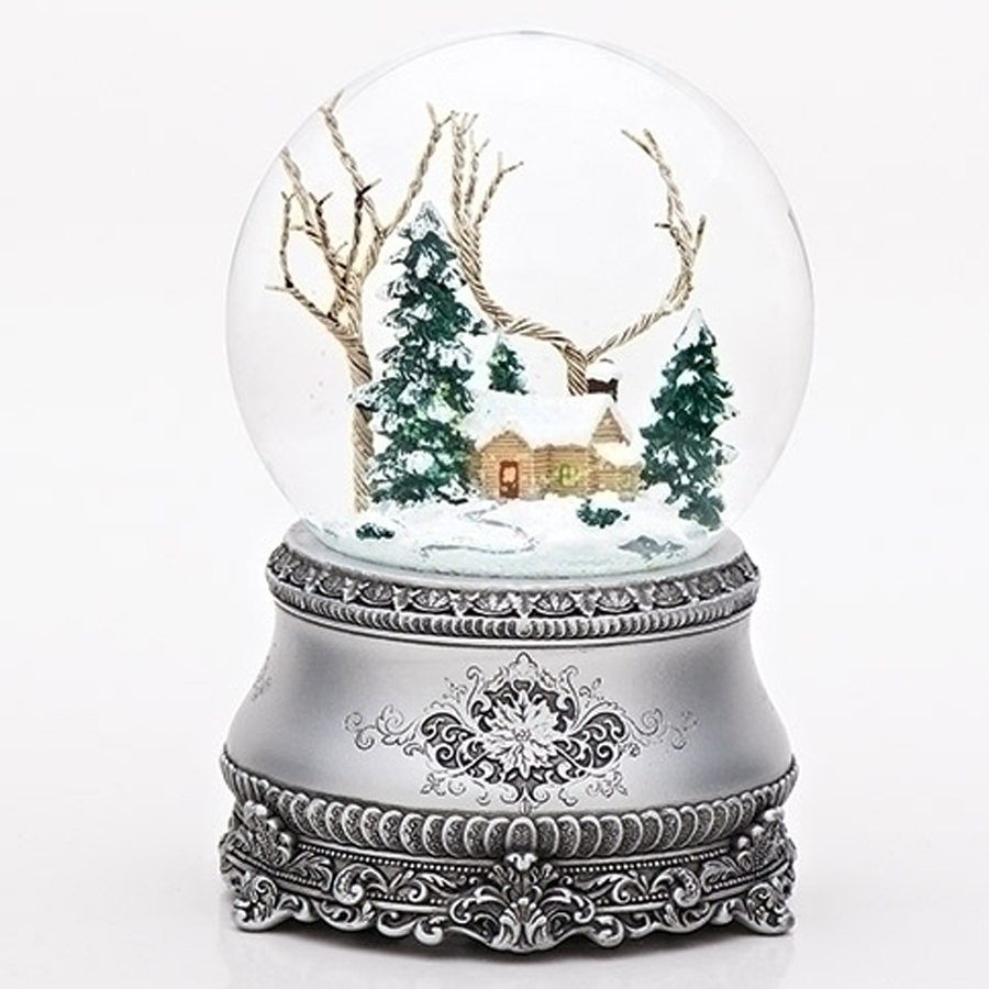 Musical snow globe with a cabin and trees inside, antique looking, decorated silver base
