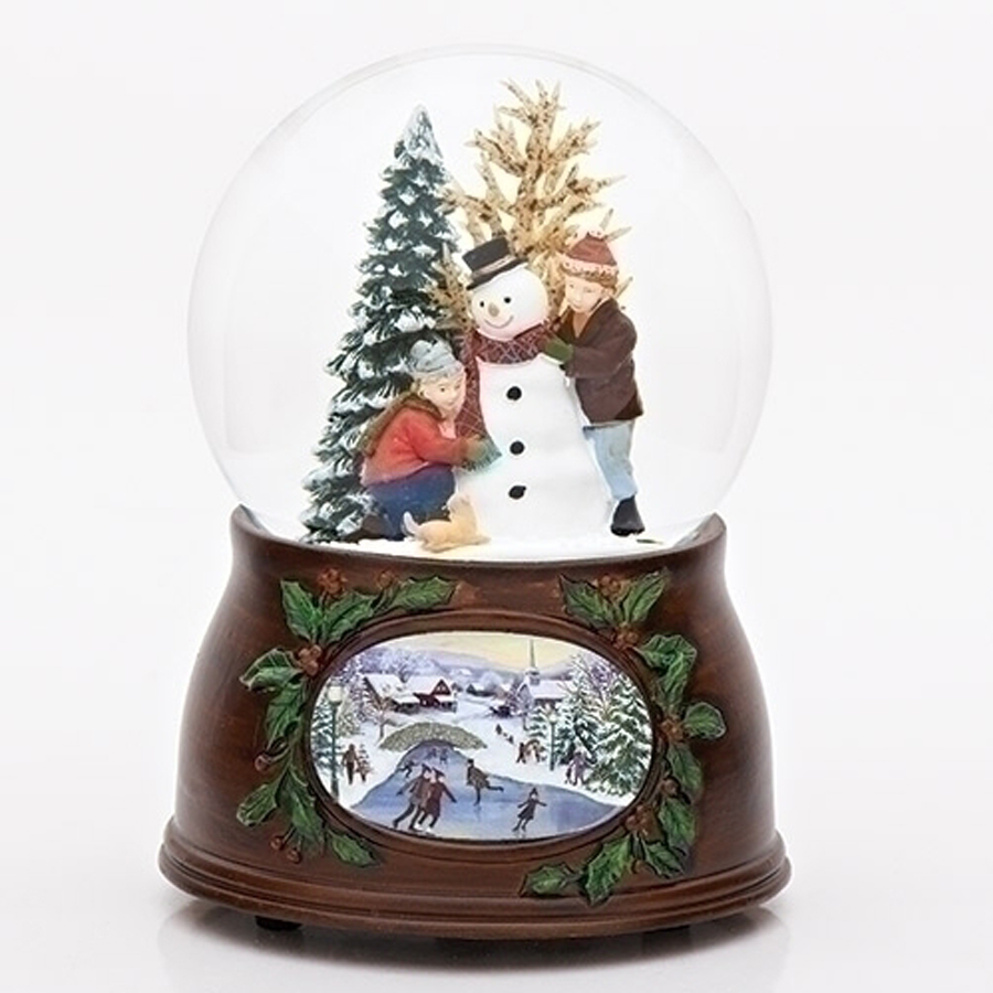 Inside the snow globe are children making a snowman with a vintage style musical base