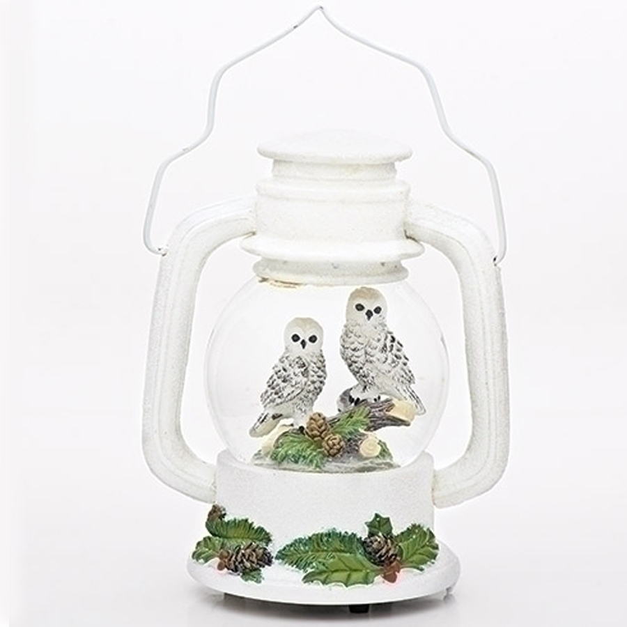 Tow owls inside a beautiful white lantern water globe with holly around the base