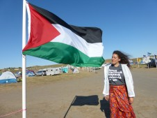 The author standing by the Palestinian flag in Oceti Sakowin Camp.