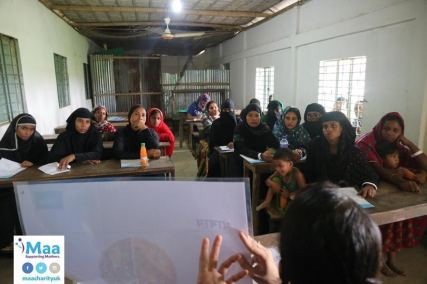 A class of women being taught basic hygiene, dietary requirements and stages of pregnancy by Jui, Maa Bangladesh Volunteer.
