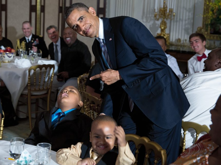 "Obama poses with a boy who fell asleep during the White House's Father's Day ice cream social on June 14, 2013. Souza remembers the president calling out, ""Pete, you've got to get a picture of this."""