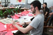 Alex writes out his final calligraphy work