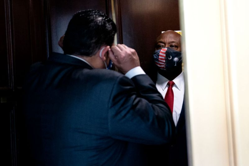 Sen. Tim Scott (R-S.C.), right, speaks to a reporter at the Russell Senate Office Building in Washington, D.C., on April 29. (Stefani Reynolds/Getty Images)