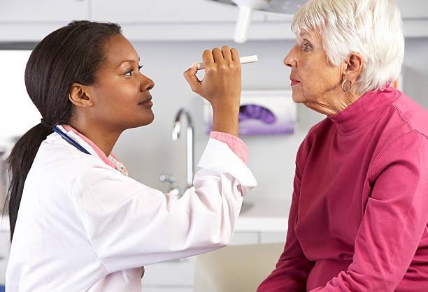 Female Doctor Examining Senior Female Patient's Eyes