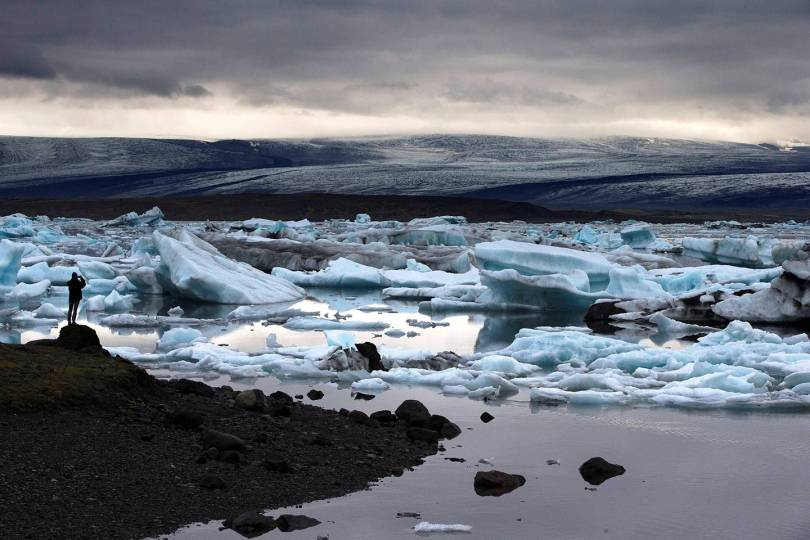 A man takes a picture of blue icebergs in Jokulsarlon, the largest glacier lagoon in Iceland, on July 8, 2014. AFP PHOTO / JOEL SAGET / AFP PHOTO / JOEL SAGET
