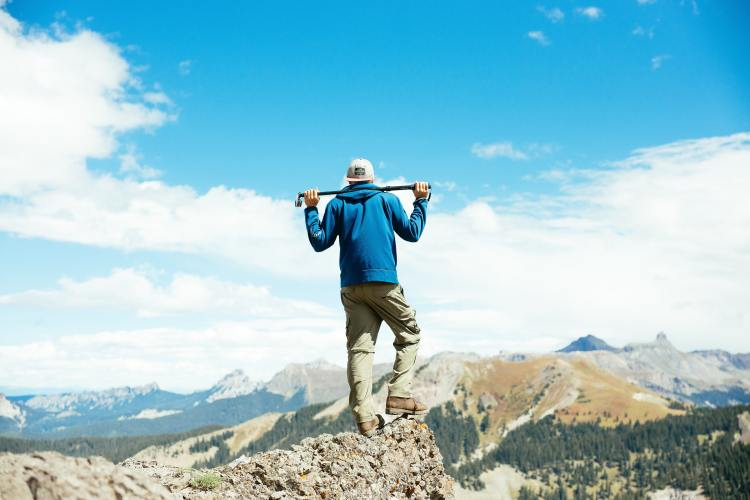 A hiker on a mountaintop in Uncompahgre National Forest