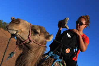 Meredith Leung riding on the back of a dromedary camel Camelus dromedarius in the Sahara Desert in Morocco on Semester at Sea Spring 2016 Photo Credit Zack Neher