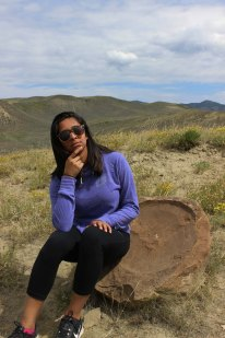 Mona Kamath sitting on a specimen of Placenticeras meeki, a giant ammonite, at the Kremmling Cretaceous Ammonite Locality in Kremmling Colorado Photo Credit Zack Neher
