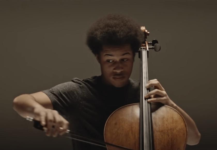 Sheku Kanneh-Mason plays cello against a dark backdrop.