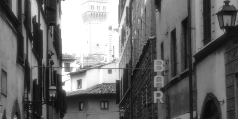 Street in Florence, Italy, with BAR sign in foreground and Palazzo Vecchio tower in background. Photo by Steve Netsky.