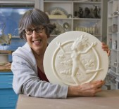 Lindley Briggs holds a plaster model for a medallion.