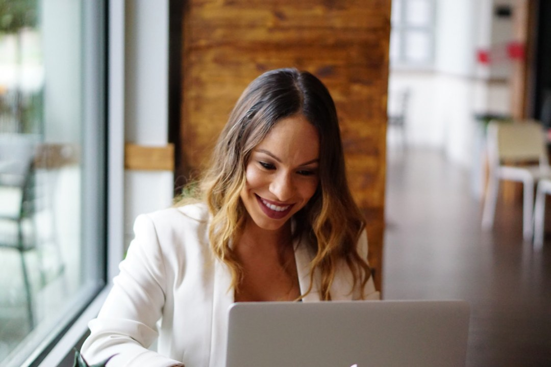 Latina woman with white blazer on laptop
